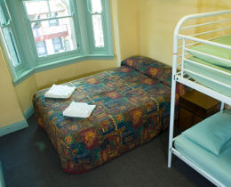 A bedroom with a window, a bed and a double bunk at the Highfield Hotelv.