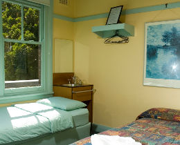 A bedroom showing a bed, a window and trees outside at the Highfield Hotel, Potts Point.